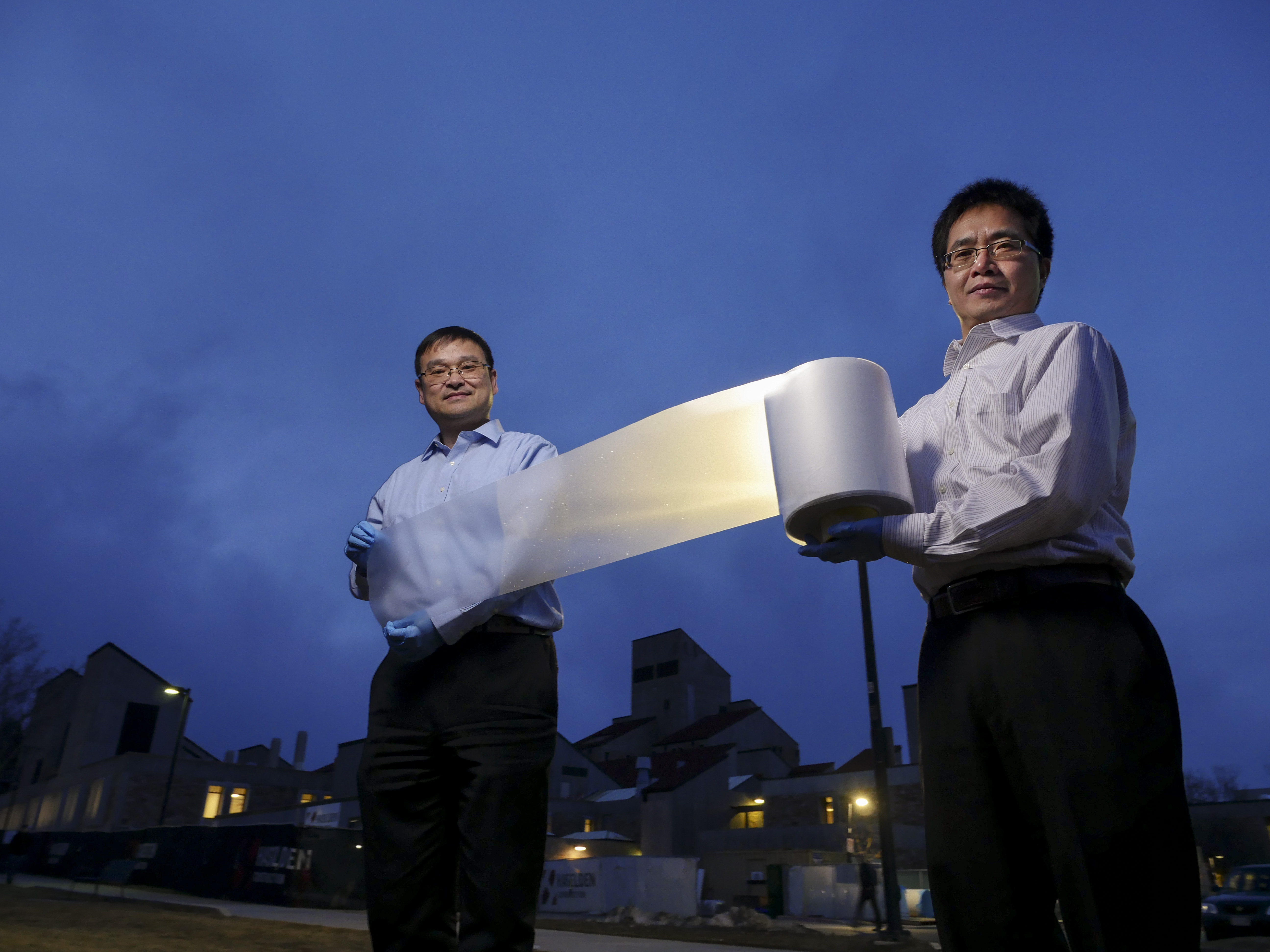 CU Boulder mechanical engineering professors Ronggui Yang, right, and Xiaobo Yin, extends a roll of their special cooling polymer film that they and their team developed near the Engineering Center in Boulder. It's a scalable ,manufactured metamaterial Ñ an engineered material with extraordinary properties not found in nature to act as a kind of air conditioning system for structures. It has the ability to cool objects even under direct sunlight with zero energy and water consumption. When applied to a surface, the metamaterial film cools the object underneath by efficiently reflecting incoming solar energy back into space while simultaneously allowing the surface to shed its own heat in the form of infrared thermal radiation. (Photo by Glenn Asakawa/University of Colorado)
